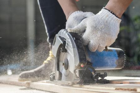 Cieśla używa kółkową saw dla ciąć drewniane deski.
