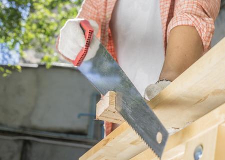 Carpinteiro, segurando uma serra manual na bancada Foto de archivo