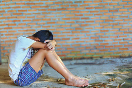 Sad, lonely, unhappy, disappointed child sitting alone emotional stress and pain, afraid, restricted, trapped, call for help, struggle, terrified, violence, slave, Human Rights Day concept. Stock Photo