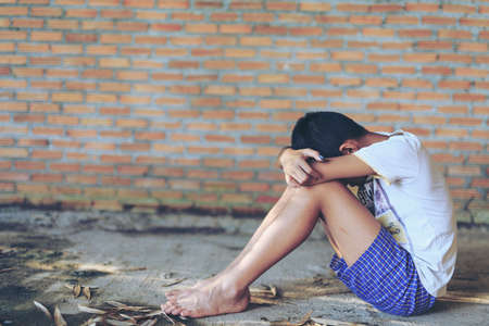 call for help: Sad, lonely, unhappy, disappointed child sitting alone emotional stress and pain, afraid, restricted, trapped, call for help, struggle, terrified, violence, slave, Human Rights Day concept. Stock Photo