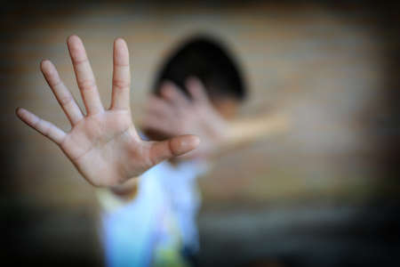 call for help: Stop abusing boy Children violence. boy, lad with her hand extended signaling to Stop,child bondage in angle of abandoned building image blur and pain, afraid, restricted, trapped, call for help, struggle, terrified, violence, slave, Human Rights Day conc