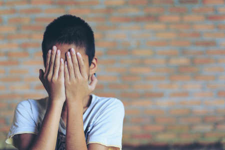 niños abandonados: A fearful child in angle of abandoned building image blur Children violence. boy, lad with her hand extended signaling to Stop,child bondage in angle of abandoned building image blur and pain, afraid, restricted, trapped, call for help, struggle, terrifie