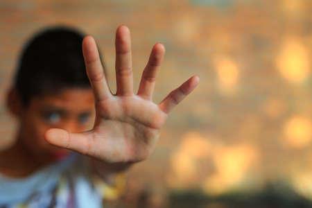 Les enfants de la violence. garçon, jeune homme avec sa main tendue de signalisation pour arrêter les enfants de la violence. garçon, jeune homme avec sa main tendue de signalisation pour arrêter, la servitude pour enfant dans l'angle d'abandon flou de l'image de la construction et de la douleur, peur, restreint, pris au piège, appeler à l'aide, struggl Banque d'images - 71053940