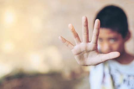 Les enfants de la violence. garçon, jeune homme avec sa main tendue de signalisation pour arrêter les enfants de la violence. garçon, jeune homme avec sa main tendue de signalisation pour arrêter, la servitude pour enfant dans l'angle d'abandon flou de l'image de la construction et de la douleur, peur, restreint, pris au piège, appeler à l'aide, struggl Banque d'images - 71053452