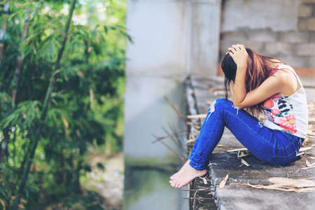 Teenager with depression sitting alone on abandoned buildings