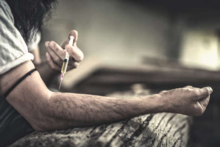 junky: Drug addict young man with syringe in action, Drug abuse concept.,