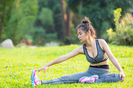 Beautiful fit young woman public park fitness stretching Stock Photo