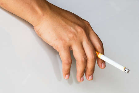 Bad habit. Close up of cigarette in hands of young girl holding it and smoking