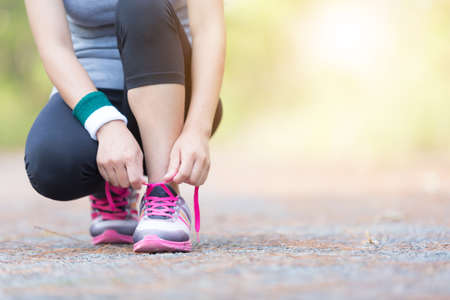 Asia woman runner jogging exercise alone to lose fat weight tying shoelaces