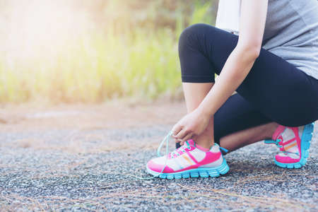 shoelace: Asia woman runner jogging exercise alone to lose fat weight tying shoelaces