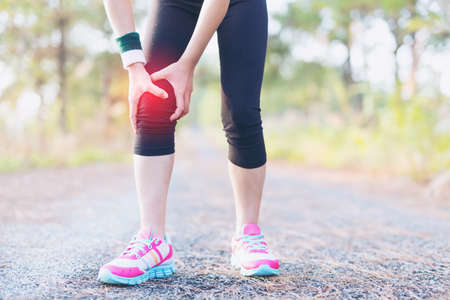スポーツ傷害を実行しています。女性アスリート ランナーによる痛みの足に触れます。 写真素材