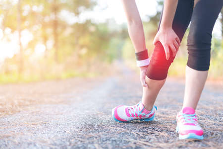 contracture: Running sport injury . Female athlete runner touching foot in pain due.