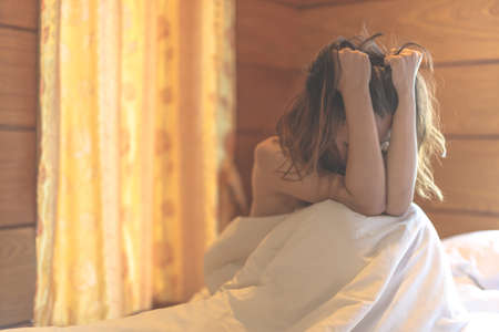 woman sit on a bed in a bedroom - concept photo of Sexual assault