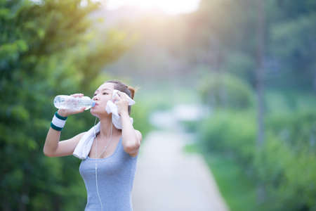 Women drink water after exercising.