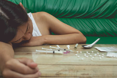 Drug addict young woman with syringe in action, Drug abuse concept. Stock Photo