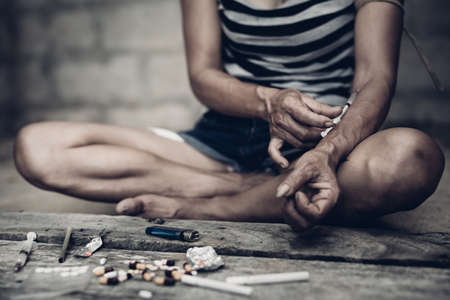 banned: Drug addict young woman with syringe in action, Drug abuse concept. Stock Photo