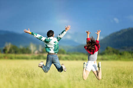 thrilled: Young people are jumping happily in the meadow.