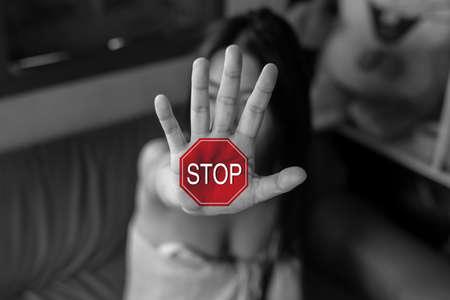 Detener, mujer de pie con la mano extendida mostrando la parada, concepto de violencia.