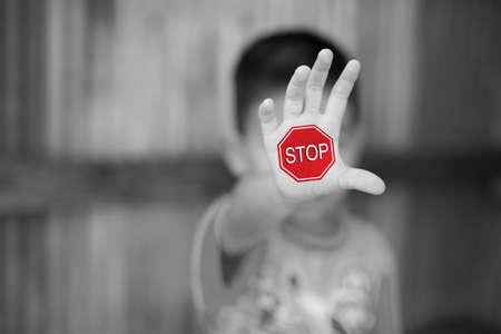 Stop, niño de pie con la mano extendida mostrando stop, concepto de violencia.