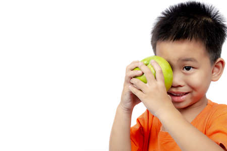 Child in orange outfit hold green apple on white background.
