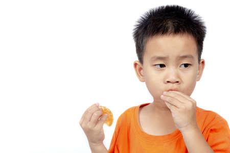 Child in orange outfit eat orange isolated on white background. Archivio Fotografico
