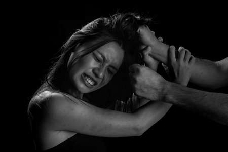 Victim of domestic violence, Human trafficking concept, End to violence against women,Scared woman with man's hand covering her head