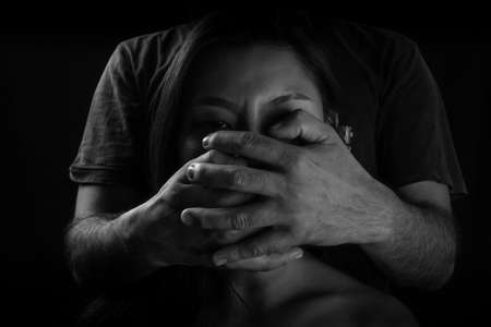 Victim of domestic violence, Human trafficking concept, End to violence against women,Scared woman with man's hand covering her mouth, Stock Photo