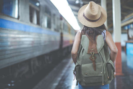 Traveler girl with a backpack traveling to the train station. Travel ideas Foto de archivo