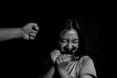 Gewalt gegen Frauen verhindern, Alle reden und nichts tun. Opfer häuslicher Gewalt, Konzept des Menschenhandels, Ende der Gewalt gegen Frauen, Angst vor einer Frau mit Männerhand, die ihren Kopf bedeckt, Sexuelle Gewalt gegen Frauen Standard-Bild