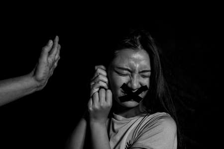 Preventing violence against women, All talk and no action. Victim of domestic violence, Human trafficking concept, End to violence against women,Scared woman with mans hand covering her head, Sexual violence against women