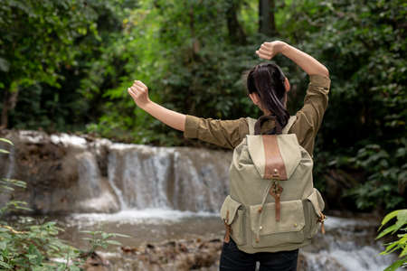 Female tourists are happy and refreshed at the waterfall. Stock Photo