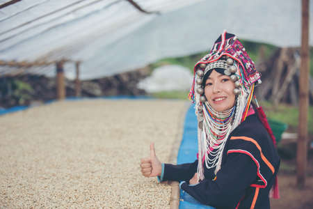 Akha women smiled and admired the coffee that was dried in the house, the hill tribe coffee products of northern Thailand. Imagens - 116068273