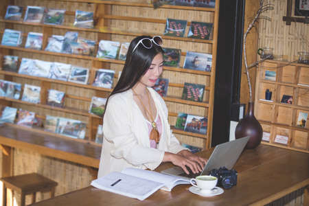 Female tourists who are working online using electronic communication devices.