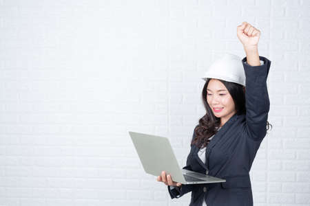 Engineering woman holding a separate notebook, white brick wall Made gestures with sign language. Stock Photo