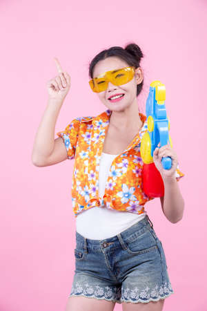 Happy girl holding a pink background water gun. Stock Photo