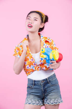 Happy girl holding a pink background water gun. 写真素材 - 120398340