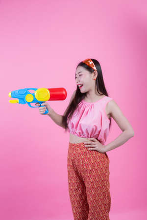 A woman dressed in a traditional Thai folk clothes holding a water gun on a pink background.