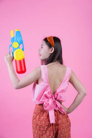 A woman dressed in a traditional Thai folk clothes holding a water gun on a pink background. 写真素材 - 120398351