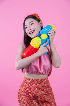 A woman dressed in a traditional Thai folk clothes holding a water gun on a pink background. Banque d'images - 120398354