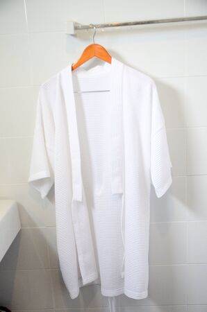 bathrobes: White bathrobes hanging in bathroom.