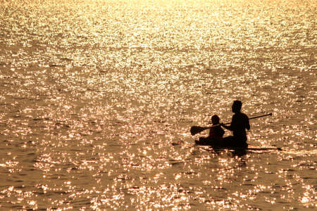 Silhouette family kayaking in the sea photo