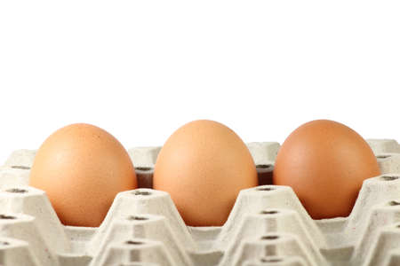 Three brown eggs in paper tray photo