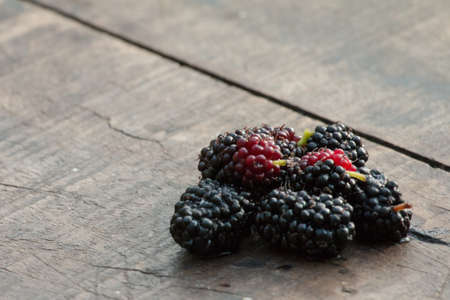 organic mulberry on wooden background photo