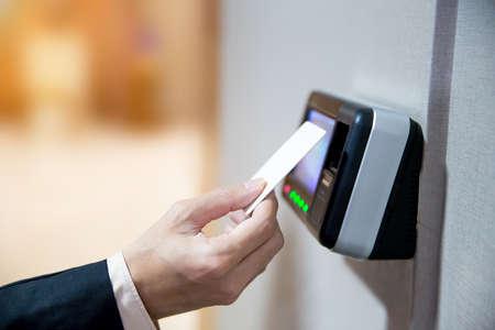 Primo piano dell'uomo d'affari della mano facendo uso della carta chiave per aprire la porta.