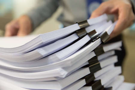 Businessman hands working in Stacks of paper files for searching information on work desk office Stock fotó - 131726930