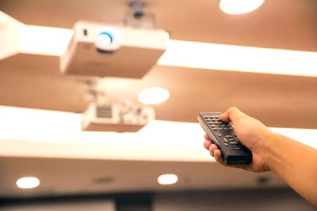 Encendido remoto, control remoto en primer plano de la mano presiona el botón en el control remoto para encender / apagar el proyector o poner la pantalla en blanco para ahorrar energía.