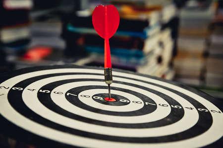 Roter Pfeil, der in der Zielmitte der Dartscheibe auf Bullseye für das Geschäftsfokuskonzept schlägt.