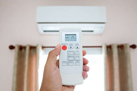 Remote control in hand closeup,Presses the button on the remote control switch to set air conditioners temperature Stok Fotoğraf