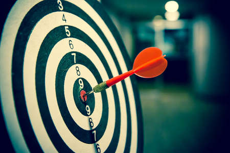 Red dart arrow  hitting in the target center of dartboard on bullseye for Business focus performance and target group concept.