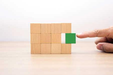 Hand choose wooden cube stacked without graphics for Business design concept and activity for child foundation practice skills.